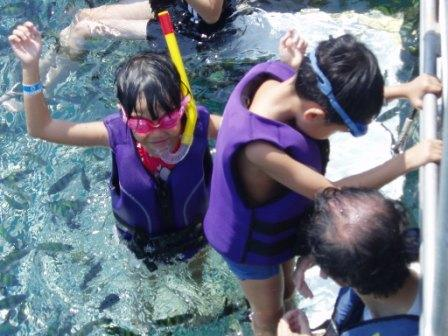 children prepare to get into water for snorkeling